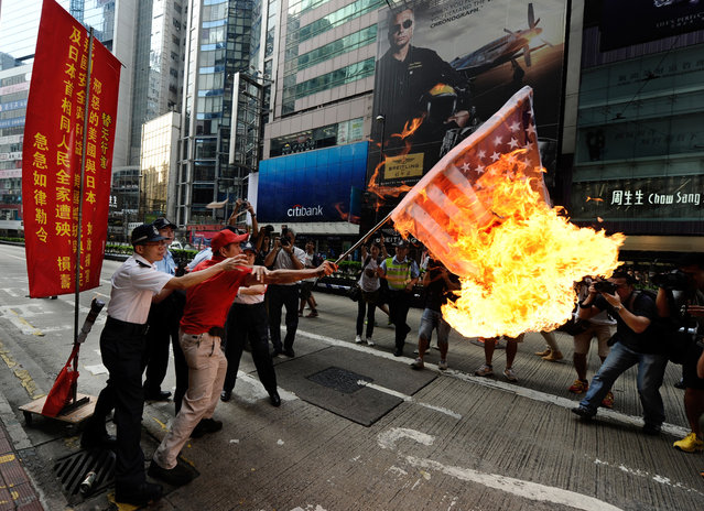 An activist waves a burning Japan-US combined flag during a demonstration over a group of disputed islands, as people make their way to the Japanese consulate in Hong Kong, on September 16, 2012. (Photo by Antony Dickson/AFP Photo)
