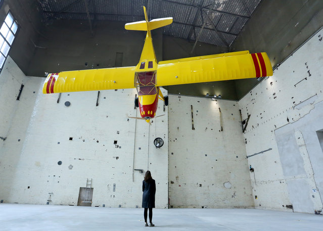 """A woman stands under the installation """"Kitfox Experimental"""" by Swiss artist Roman Signer in the kettle building at the newly opened Kindl Center for Contemporary Art in Berlin, Germany, 12 September 2014. The privately funded institution will be an exhibition and event location for international modern art.  (Photo by Stephanie Pilick/EPA)"""
