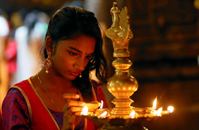 A devotee lights oil lamps at a religious ceremony during the Diwali or Deepavali festival at a Hindu temple in Colombo, Sri Lanka October 18, 2017. (Photo by Dinuka Liyanawatte/Reuters)