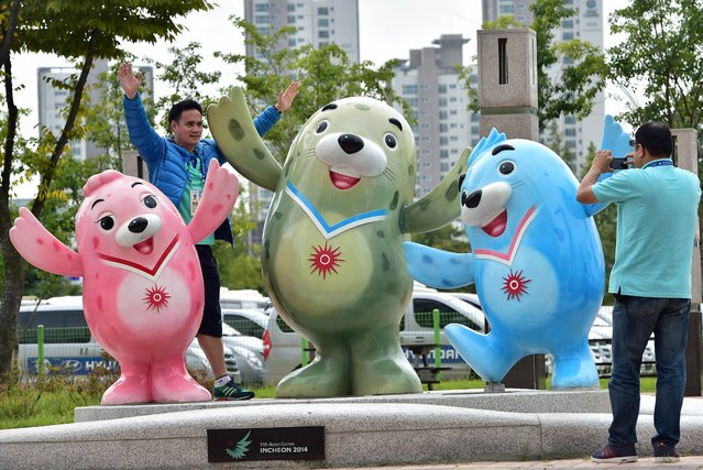 Journalists take pictures with mascots of the 17th Asian Games outside the main press center in Incheon on September 17, 2014. The 17th Asian Games will open in Incheon, South Korea on September 19, with 45 nations and territories competing in 36 sports ranging from athletics and swimming to kabaddi and sepak takraw. (Photo by Jung Yeon-Je/AFP Photo)