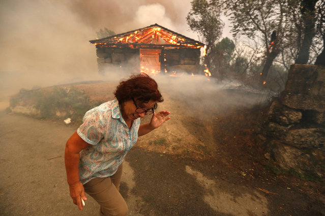A woman runs away from a burning house at the small village of Oteiro, near Sao Pedro do Sul, Portugal August 13, 2016. (Photo by Rafael Marchante/Reuters)