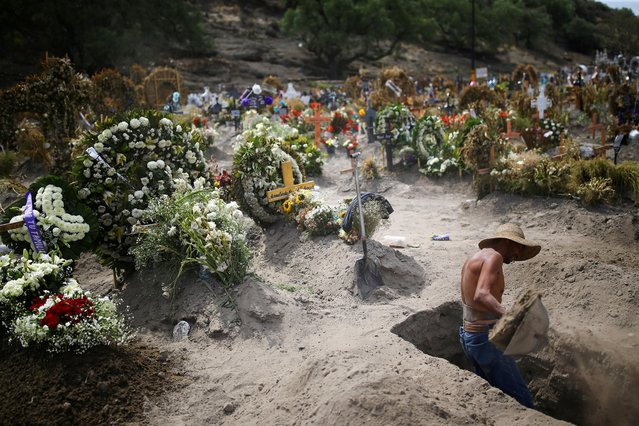 A cemetery worker dig new graves at the Xico cemetery on the outskirts of Mexico City, as the coronavirus disease (COVID-19) outbreak continues in Mexico, June 10, 2020. (Photo by Edgard Garrido/Reuters)