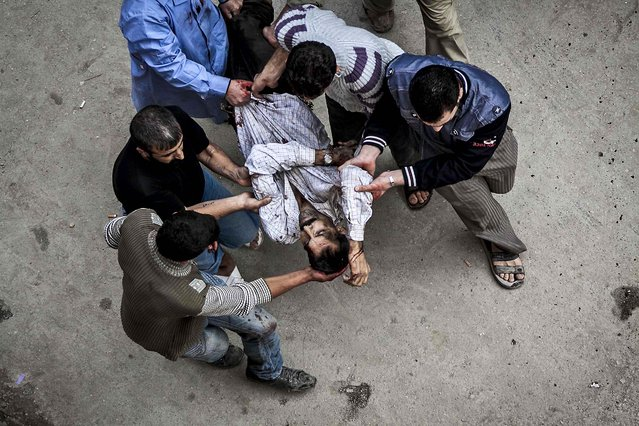 Syrian residents carry a man severely injured from an artillery shell that landed near a bakery in Aleppo, Syria October 23, 2012. Severa peoplel were killed and a dozen were injured. (Photo by Narciso Contreras/Associated Press)