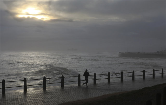 A woman runs on the promenade in stormy weather in Sea Point, Cape Town, South Africa, Friday, May 29, 2020. With dramatically increased community transmissions, Cape Town has become the center of the coronavirus outbreak in South Africa. (Photo by Nardus Engelbrecht/AP Photo)