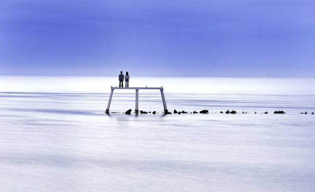 "A calm and tranquil North Sea laps against the art installation, ""The Couple"" by artist Sean Henery just off the coast at  Newbiggin-by-the-Sea, in north east England, as the warmer than usual temperatures continue across the United Kingdom, Monday September 29, 2014. Much of the country is still experiencing temperatures in the low 20's Celsius when the average for September is nearer 16 Celsius. (Photo by Owen Humphreys/AP Photo/PA Wire)"