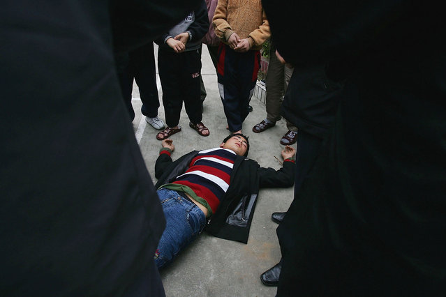 A Chinese boy  faints after refusing to eat at an assistance center February 23, 2005 in Shenzhen, Guangdong Province, China. (Photo by Cancan Chu/Getty Images)