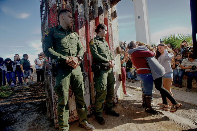 """Cristal Brayan Ramirez Cervantes hugs Lucia Cervantes, while daughters Brenda Karely and Ashley de la Torres Ramirez look on atthe U.S. Mexico border November 18, 2017 in San Ysidro, California. The event, """"Abriendo La Puerta De La Espernaza"""", or """"Opening The Door of Hope"""", was put on to reunite families who have been separated by deportation. (Photo by Sandy Huffaker/Getty Images)"""