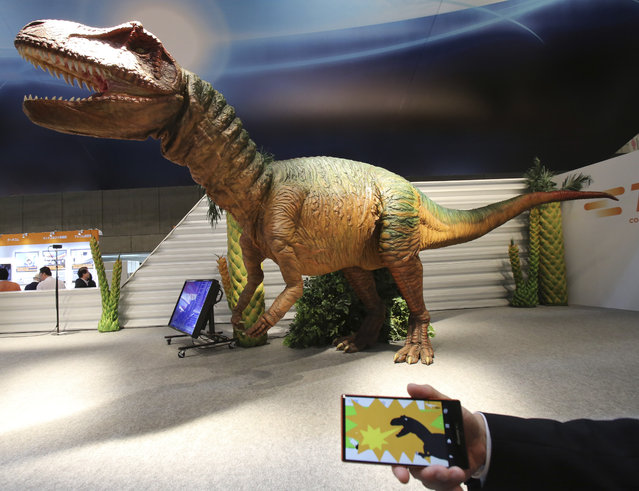 """A TE Connectivity Japan staff member demonstrates how to control remotely its dinosaur robot """"TE Saurus"""" by a smart phone during the annual CEATEC Japan advanced technologies show in Chiba, east of Tokyo Tuesday, October 7, 2014. With a Sharp Aquos ZETA mobile phone model, users can make the 6.5-meter (21 feet, 4 inches) long, 2.1-meter (6 feet, 11 inches). (Photo by Koji Sasahara/AP Photo)"""