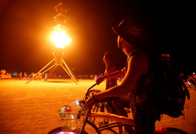 Participants watch the flames on the Spire of Fire as approximately 70,000 people from all over the world gather for the 30th annual Burning Man arts and music festival in the Black Rock Desert of Nevada, U.S. August 29, 2016. (Photo by Jim Urquhart/Reuters)