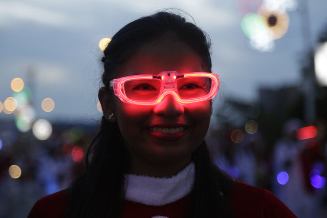 Estefani Garcia wears illuminated glasses as she marches in a music band during the annual Christmas parade in Panama City, Sunday, December 10, 2017. (Photo by Arnulfo Franco/AP Photo)