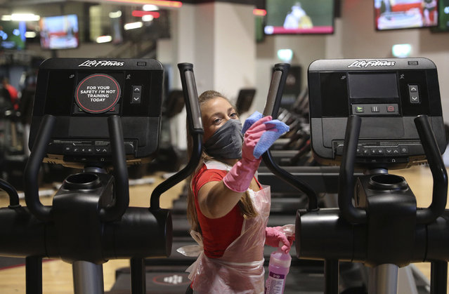 General manager Tori Waight cleans a cross trainer at DW Fitness First in Basingstoke, England, Saturday July 25, 2020, as fitness gyms are allowed to admit members of the public for the first time since the national lockdown.  re-opening as Indoor gyms, swimming pools and sports facilities can reopen as part of the latest easing of coronavirus lockdown measures in England. (Photo by Andrew Matthews/PA Wire via AP Photo)