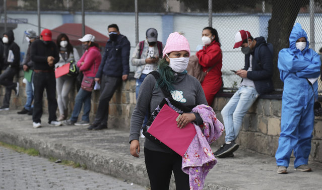 People wait in line to get COVID-19 tests, outside a health clinic in Quito, Ecuador, Wednesday, July 29, 2020. The Ecuadorian capital has experienced a surge in COVID-19 cases since the government started to reopen the economy last month. (Photo by Dolores Ochoa/AP Photo)