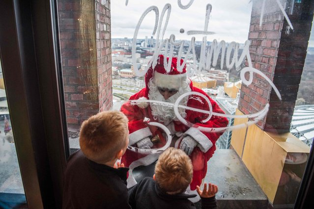 A man dressed as Father Christmas aka Santa Claus entertains children on the top of the Kollhoff tower on December 17, 2017 as part of a yearly stunt before the festive season. (Photo by John MacDougall/AFP Photo)
