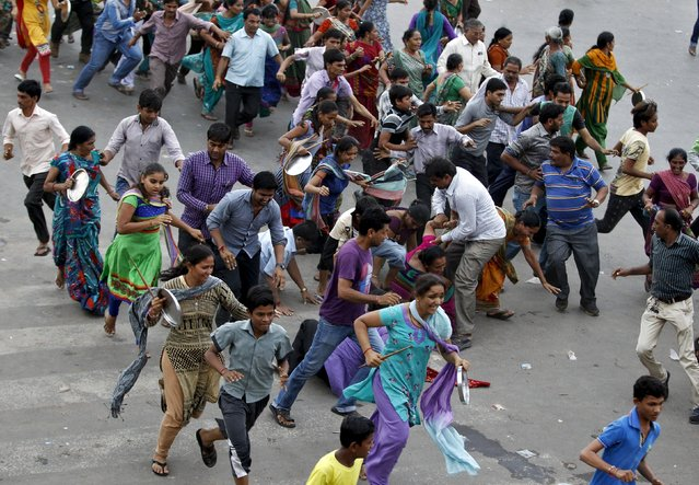 Members of the Patel community run as they are dispersed by Indian police during a protest rally in Ahmedabad, India, September 19, 2015. Thousands of the community members on Saturday protested against the detention of Hardik Patel, who is leading the movement to demand reservation benefits for the community, local media reported. (Photo by Amit Dave/Reuters)