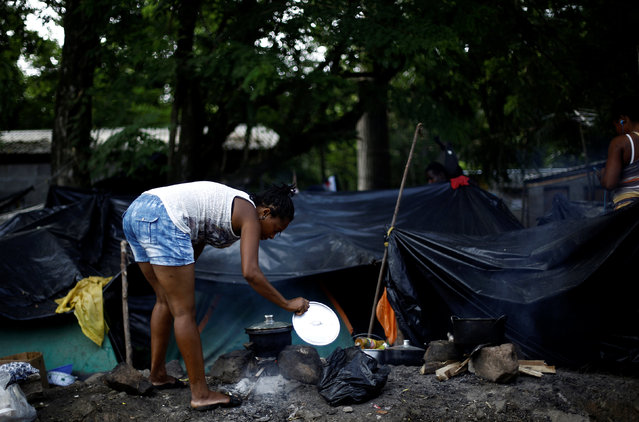 An African migrant stranded in Costa Rica cooks food in a makeshift camp at the border between Costa Rica and Nicaragua, in Penas Blancas, Costa Rica, September 8, 2016. (Photo by Juan Carlos Ulate/Reuters)