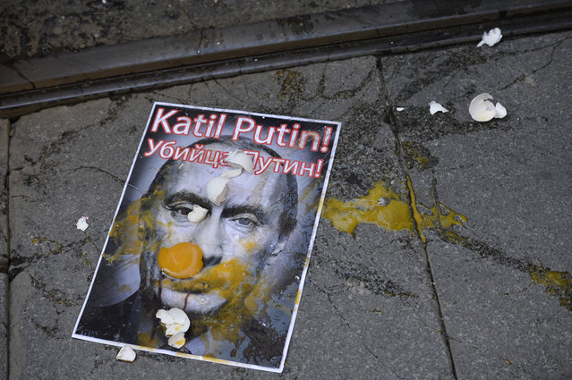 A picture depicting Russian President Vladimir Putin is splattered with eggs during a protest against Russian military operations in Syria, in Istanbul, Turkey, Saturday, October 3, 2015. The picture reads both in Turkish and Russian: 'Murderer Putin'. In ramping up its military involvement in Syria's civil war, Russia appears to be betting that the West, horrified by Islamic State's atrocities, may be willing to tolerate Syrian President Bashar Assad for a while, perhaps as part of a transition. (Photo by AP Photo)