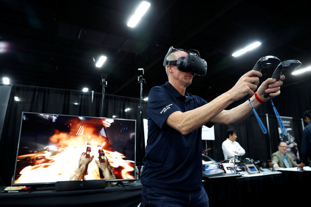 John Cummins, sales and marketing senior vice president for DisplayLink, demonstrates the company's DisplayLink XR reference design with a wireless virtual reality game, during CES Unveiled at the 2018 CES in Las Vegas, Nevada, U.S. January 8, 2018. (Photo by Steve Marcus/Reuters)