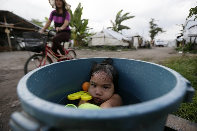 Kyra Marie Montano,3, takes a bath inside a pail  at a tent city in San Jose Village which was damaged by the 2013 Typhoon Haiyan in Leyte province, Philippines, 07 November 2014. Super Typhoon Haiyan, one of the world's strongest cyclones, slammed into the eastern and central Philippines on 08 November 2013 killing more than 7,300 people and displacing over 4 million. (Photo by Dennis M. Sabangan/EPA)