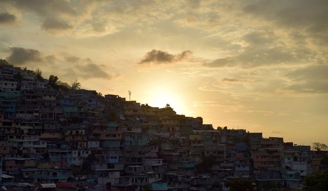 The sun sets over crowded housing in Jalousie neighborhood of Petion Ville commune in the Haitian capital Port-au-Prince, on June 12, 2017. (Photo by Hector Retamal/AFP Photo)