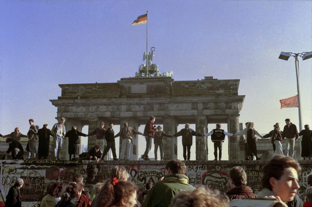 In this November 10, 1989 file photo Berliners sing and dance on top of The Berlin Wall to celebrate the opening of East-West German borders. Thousands of East German citizens moved into the West after East German authorities opened all border crossing points to the West. In the background is the Brandenburg Gate. (Photo by Thomas Kienzle/AP Photo)