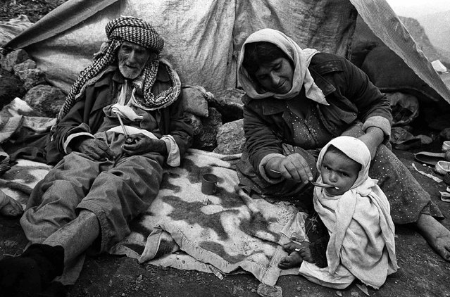 Iraqi Kurdish refugees sit in front of a tent in Cukurca refugee camp in Turkey April 8, 1991. (Photo by Srdjan Zivulovic/Reuters)
