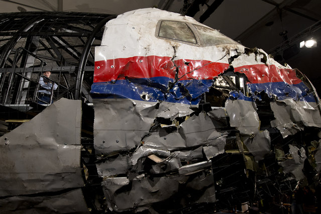 A Dutch Military Policeman, left inside, guards part of the reconstructed cockpit, right, and forward section of the fuselage after the Dutch Safety Board presented it's final report into what caused Malaysia Airlines Flight 17 to break up high over Eastern Ukraine last year, killing all 298 people on board, during a press conference in Gilze-Rijen, central Netherlands, Tuesday, October 13, 2015. (Photo by Peter Dejong/AP Photo)