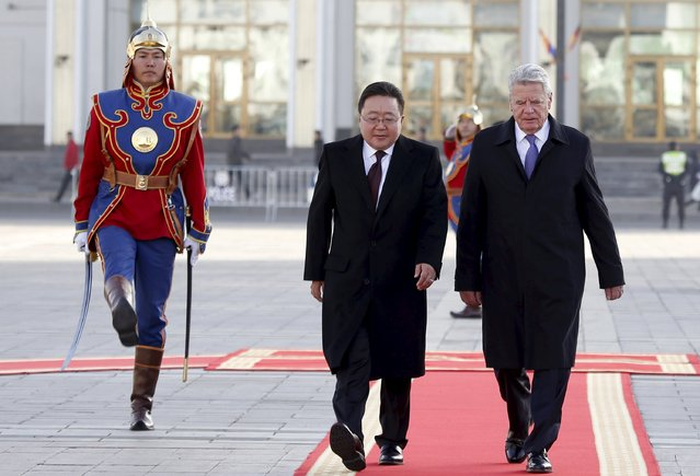 Germany's President Joachim Gauck (R) walks with his Mongolian counterpart Tsakhiagiin Elbegdorj (C) as they inspect honour guards during a welcoming ceremony outside the national parliament building at Sukhbaatar square, in Ulaanbaatar, Mongolia, October 15, 2015. (Photo by B. Rentsendorj/Reuters)