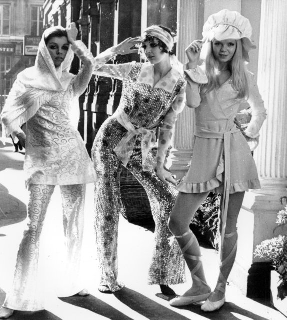 "Models pose in designs from May Quant's collection on a street in London, England, on October 16, 1969.  Grania, left, wears the ""Shimmy Shimmy,"" a white rayon dress over matching pants with a shawl.  Baba, center, wears ""Razzamatazz,"" a jumpsuit featuring plastic sequins in blue, silver and red on nylon.  Linda wears ""Muffit,"" a pink minidress with an old English style floppy mobcap. (Photo by AP Photo)"