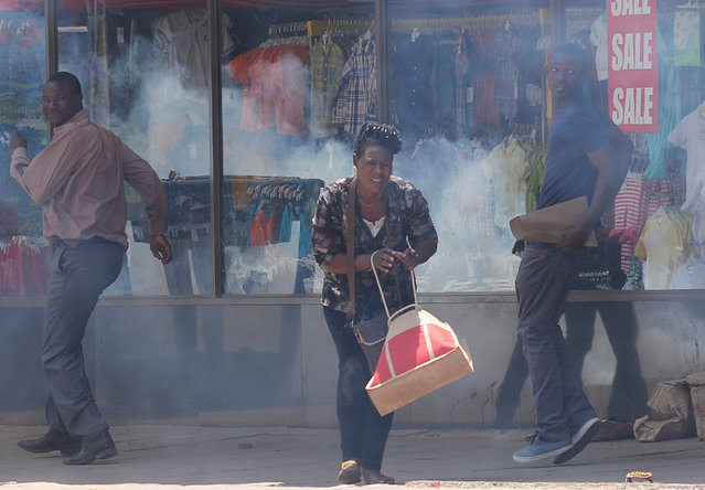 People flee teargas during clashes between police and street vendors in central Harare, Zimbabwe, September 27, 2016. (Photo by Philimon Bulawayo/Reuters)
