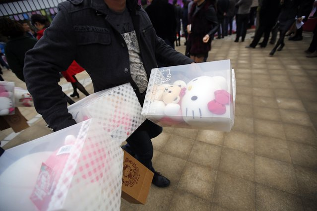 A man carries Hello Kitty plush toys during an inauguration ceremony of a Hello Kitty amusement park in Anji, Zhejiang province November 28, 2014. (Photo by Carlos Barria/Reuters)