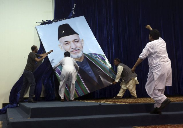 Supporters of Afghan presidential candidate Abdullah Abdullah take down a large portrait of Afghan President Hamid Karzai before a gathering in Kabul, in this July 8, 2014 file photo. (Photo by Omar Sobhani/Reuters)