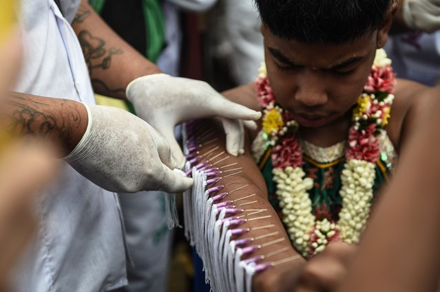 A young devotee of the Nine Emperor Gods has needles pierced through his arm during the annual Phuket Vegetarian Festival in the southern province of Phuket on October 1, 2016. (Photo by Lillian Suwanrumpha/AFP Photo)