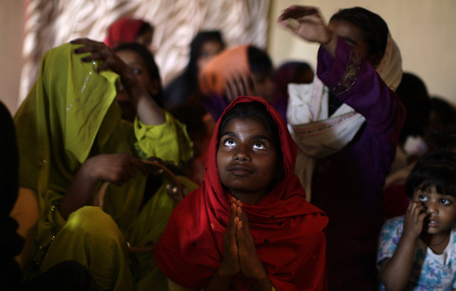Pakistani Christians pray during a Mass on Good Friday in a church in Islamabad, Pakistan, Friday, March 29, 2013. Christians around the world are marking the Easter holy week. (Photo by Muhammed Muheisen/AP Photo)