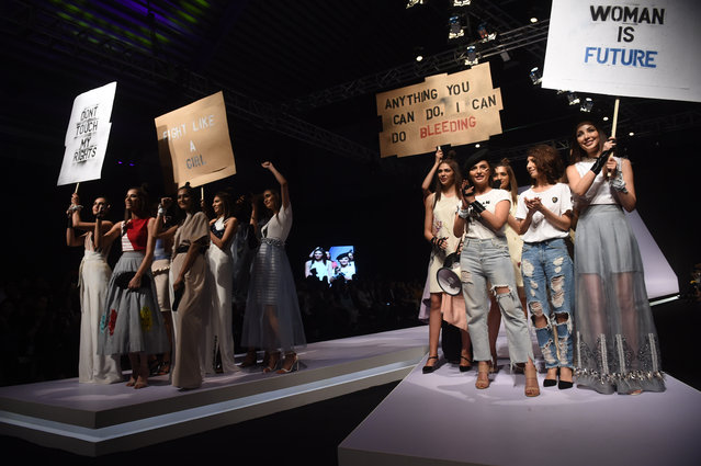 Models carry placards as they present creations by Pakistani designer Hira Ali during the first day of the Pakistan Fashion Design Council (PFDC) Fashion Week in Lahore on March 9, 2018. (Photo by Arif Ali/AFP Photo)