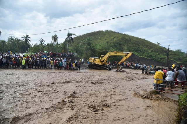 Haitians wait to cross the river La Digue in Petit Goave where the bridge collapsed during the rains of the Hurricane Matthew, southwest of Port-au-Prince, October 5, 2016. (Photo by Hector Retamal/AFP Photo)