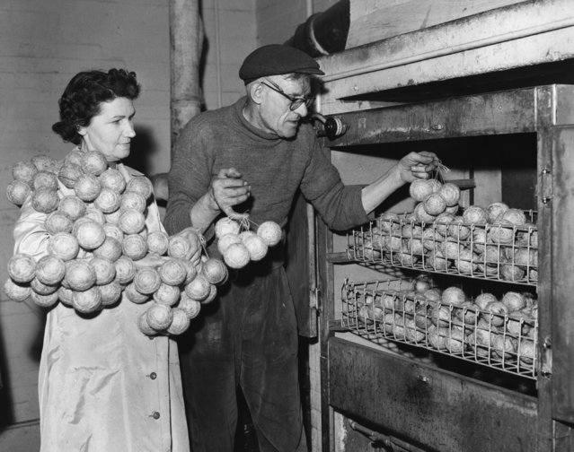 Workers at a cricket ball factory in Teston, Kent, place the centres of the balls into a heated oven in order to tighten them, March 8, 1960. (Photo by Fox Photos/Getty Images)