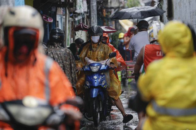 Residents wearing a face mask to prevent the spread of the coronavirus evacuate to safer grounds as rains from a typhoon locally known as Goni starts in Manila, Philippines on Sunday November 1, 2020. (Photo by Aaron Favila/AP Photo)