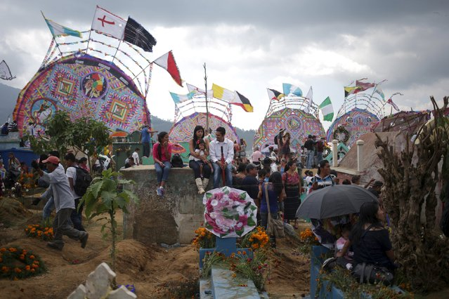 People sit at graveyards in front of giant kites in the cemetery of Santiago Sacatepequez, Guatemala, November 1, 2015. (Photo by Jorge Dan Lopez/Reuters)
