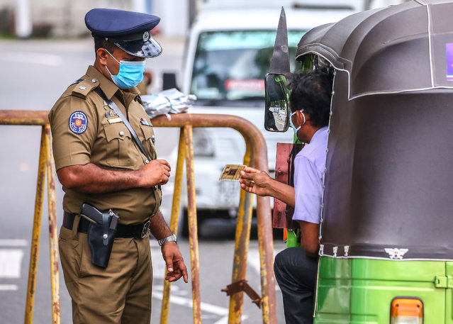 Sri Lankan police officers check vehicles in a checkpoint during a quarantine curfew, as a preventive measure against the spread of the COVID-19 in Colombo on October 25, 2020. (Photo by Saman Abesiriwardana/Pacific Press/LightRocket via Getty Images)