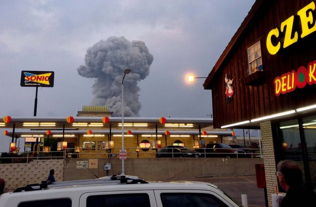 People at a Czech Stop look at a cloud of smoke rising from the explosion in West, Texas, April 17, 2013. (Photo by Andy Bartee via Dallas Morning News/MCT)