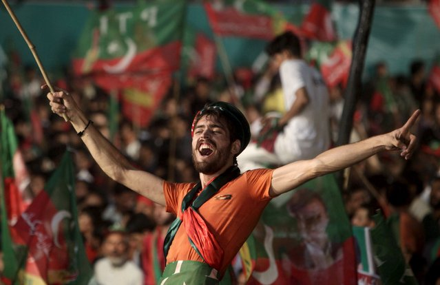 Supporters of the Pakistan Tehreek-e-Insaf (PTI) political party wave flags and shout slogans as they listen to a speech by Chairman Imran Khan during a by-election campaign rally in Lahore, Pakistan, October 9, 2015.  (Photo by Mohsin Raza/Reuters)