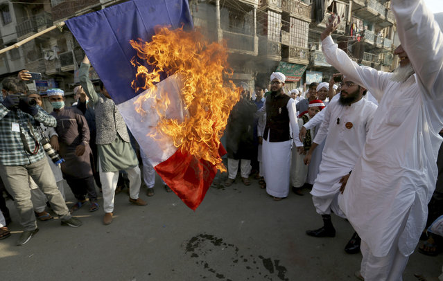 Supporters of religious group burn a representation of a French flag during a rally against French President Emmanuel Macron and republishing of caricatures of the Prophet Muhammad they deem blasphemous, in Karachi, Pakistan, Friday, October 30, 2020. Muslims have been calling for both protests and a boycott of French goods in response to France's stance on caricatures of Islam's most revered prophet. (Photo by Fareed Khan/AP Photo)