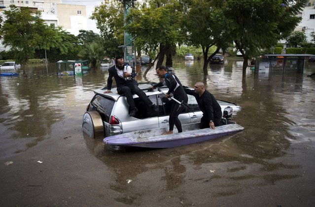 Israelis on a small motor boat help a motorist (L) after his vehicle got stuck on a flooded street in the southern city of Ashkelon, Israel, November 9, 2015. (Photo by Amir Cohen/Reuters)