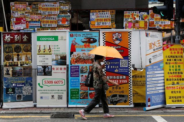 A woman walks past banners promoting retail goods and services displayed in front of closed shops for rent at the shopping Mongkok District in Hong Kong, China August 29, 2016. (Photo by Bobby Yip/Reuters)