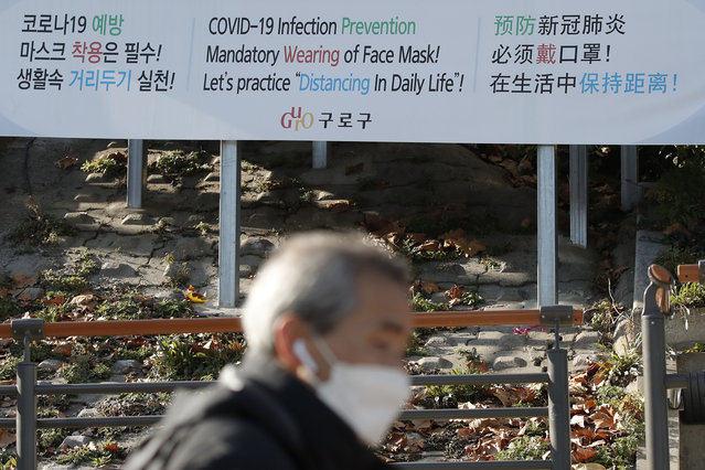A man wearing a face mask walks past a banner showing precautions against the coronavirus in Seoul, South Korea, Monday, November 23, 2020. (Photo by Lee Jin-man/AP Photo)