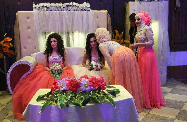 Kurdish brides Halbast Khalili, 21, (L), and Mezgin Murat, 21, (C), are greeted by the invited during their wedding reception without their grooms on November 11, 2015 near Qamishli, in the autonomous region of Rojava, Syria. They married their husbands in absentia two months after the brothers successfully immigrated to Germany in the arduous journey as refugees. The women plan to join their husbands in Europe once their immigration documents have been processed. (Photo by John Moore/Getty Images)