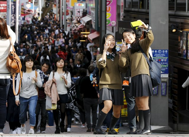 School girls pose for a selfie in the trendy Harajuku district in Tokyo, Japan, November 11, 2015. (Photo by Toru Hanai/Reuters)