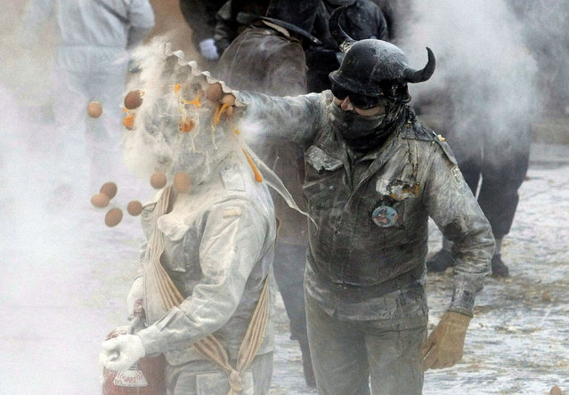"""A reveller smashes a box full of eggs on another participant during the """"Els Enfarinats"""" (The Flouring) festival in Ibi near Alicante, Spain, December 28, 2014. The fiesta is celebrated annually on the Day of Innocents, when participants dress in mock military uniforms to perform a false coup d'etat consisting in a fight with eggs, flour and fireworks. (Photo by EPA/Morell)"""