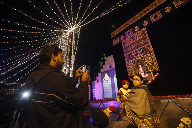 A man uses a mobile phone to take a photo of his family in front of a religious monument, during a celebration to mark Eid-e-Milad-ul-Nabi, the birth anniversary of Prophet Mohammad, in Karachi January 3, 2015. (Photo by Athar Hussain/Reuters)