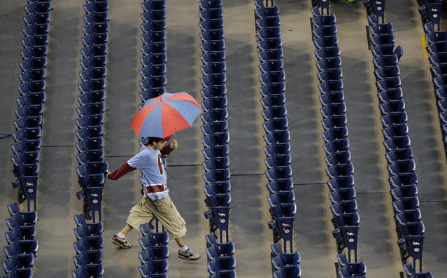 A Philadelphia Phillies' fan walks through the stands as rain delays the start of a baseball game against the Chicago Cubs, Saturday, September 12, 2015, in Philadelphia. (Photo by Matt Slocum/AP Photo)